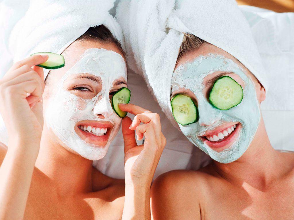 two woman with cucumber face masks on