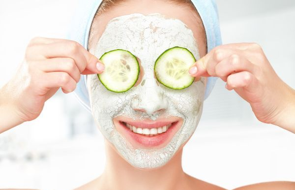 woman holding two cucumbers wearing a face mask