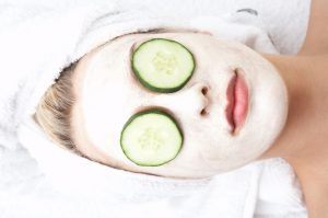woman laying down with cucumbers over her eyes wearing a face mask